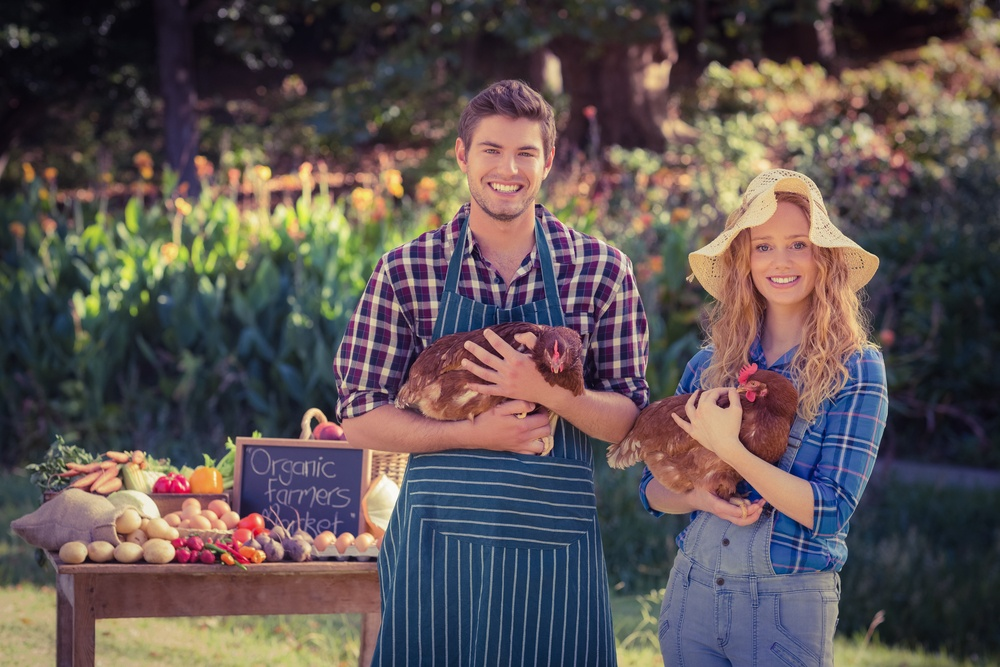 Happy farmers standing at their stall and holding chicken on a sunny day.jpeg