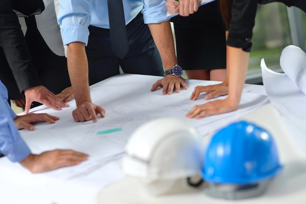 business people group on meeting and presentation  in bright modern office with construction engineer architect and worker looking building model and blueprint  plans.jpeg